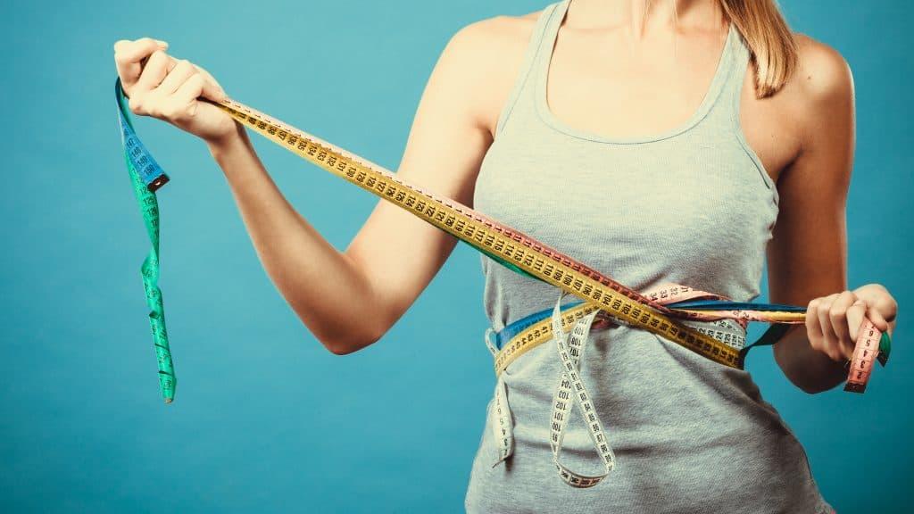 Imagem de uma mulher com fitas métricas em volta do abdômen.
