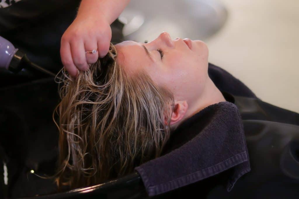 Foto de uma mulher loira de olhos fechados em um lavatório de salão de beleza, onde uma outra mulher lava o seu cabelo.