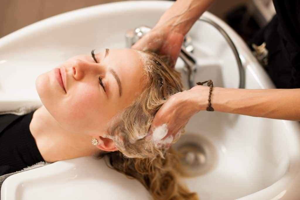 Na foto uma mulher em um lavatório de salão de beleza.