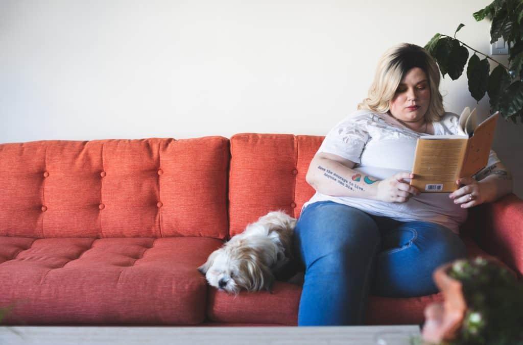 Uma mulher está sentada, ao lado de um cachorro, em um sofá vermelho enquanto lê um livro. No lado direito da imagem, há uma planta que cai em parte sobre o sofá.