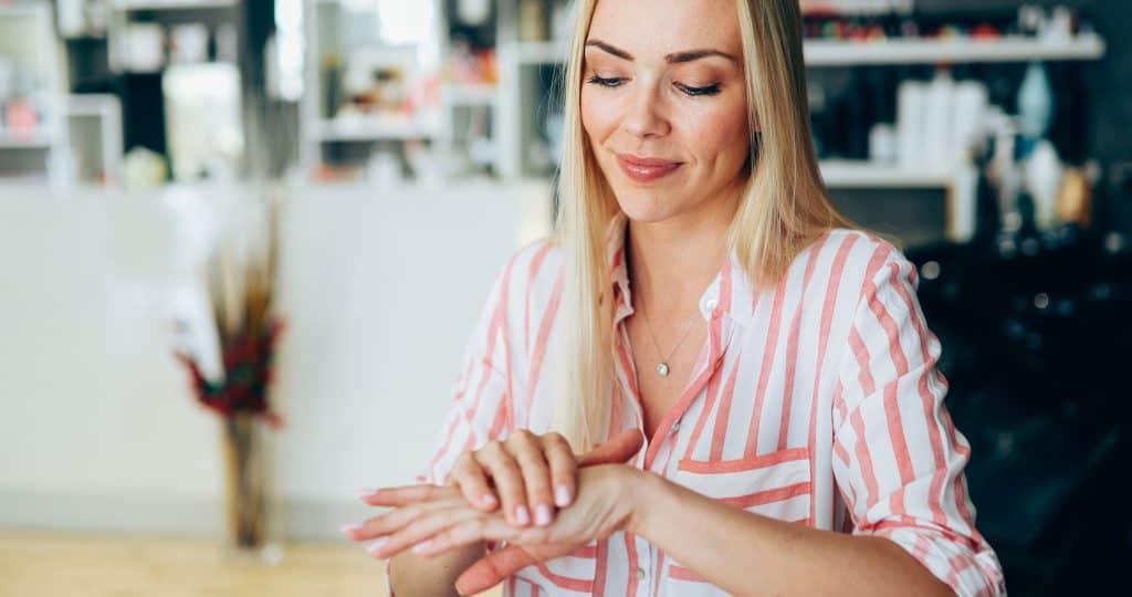 Imagem de uma mulher aplicando um creme nas mãos.