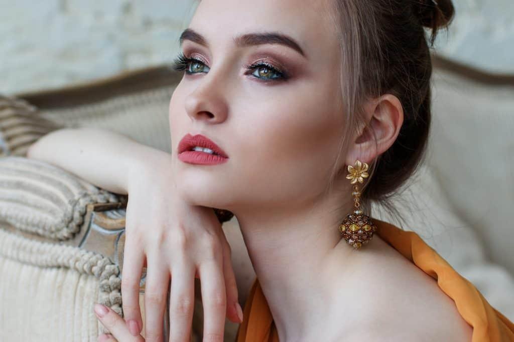 Foto de uma mulher nitidamente maquiada, com olhar longe, cabelos presos, brilho grande e um dos braços apoiado em uma poltrona.