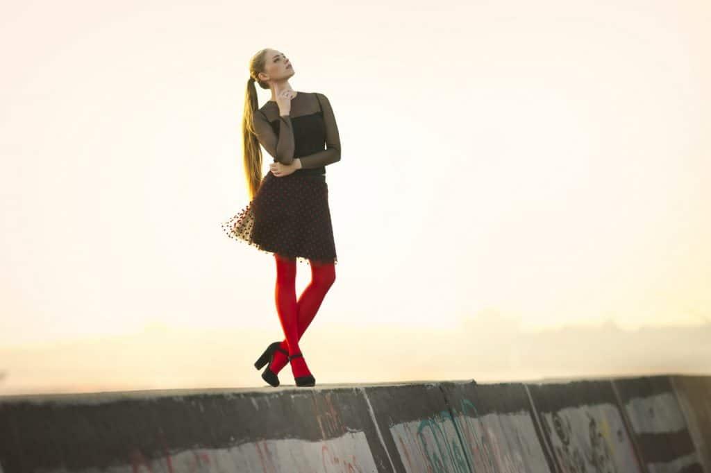 Foto de uma mulher em pé, em posição pensativa, com as perna cruzadas, vestido vestido preto de manga longa e meia calça vermelha.