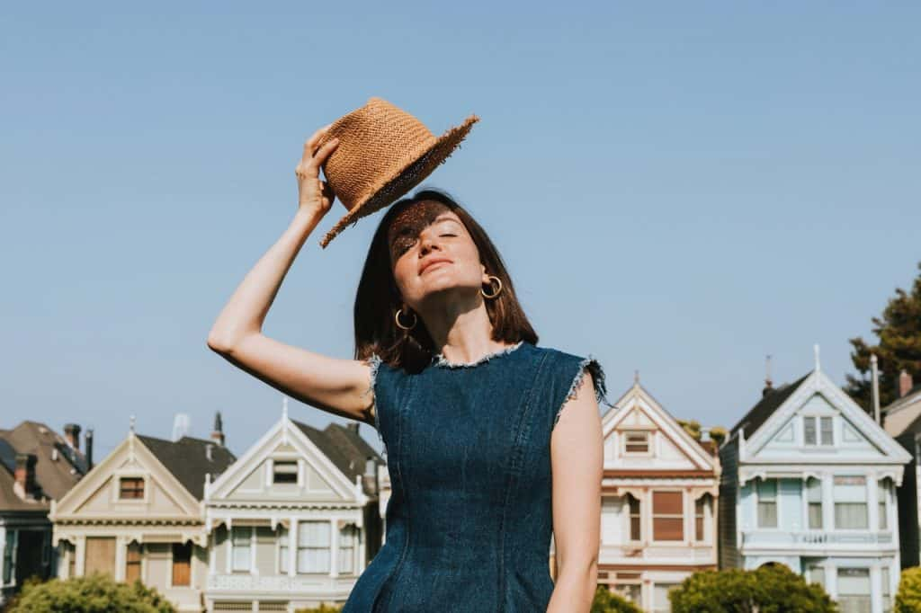 Imagem de uma mulher segurando um chapéu em dia ensolarado com as paited ladies de São Francisco, na Califórnia, ao fundo.