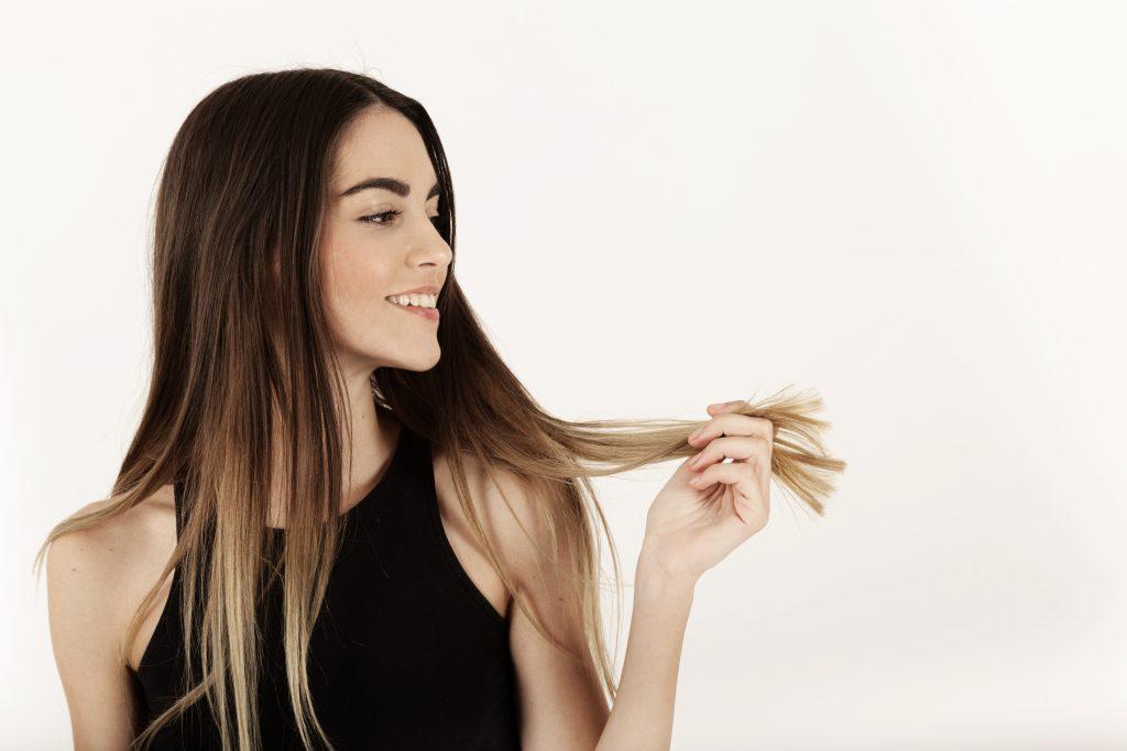 Mulher vestida com regata preta segura as pontas de seus longos cabelos castanhos com luzes californianas.