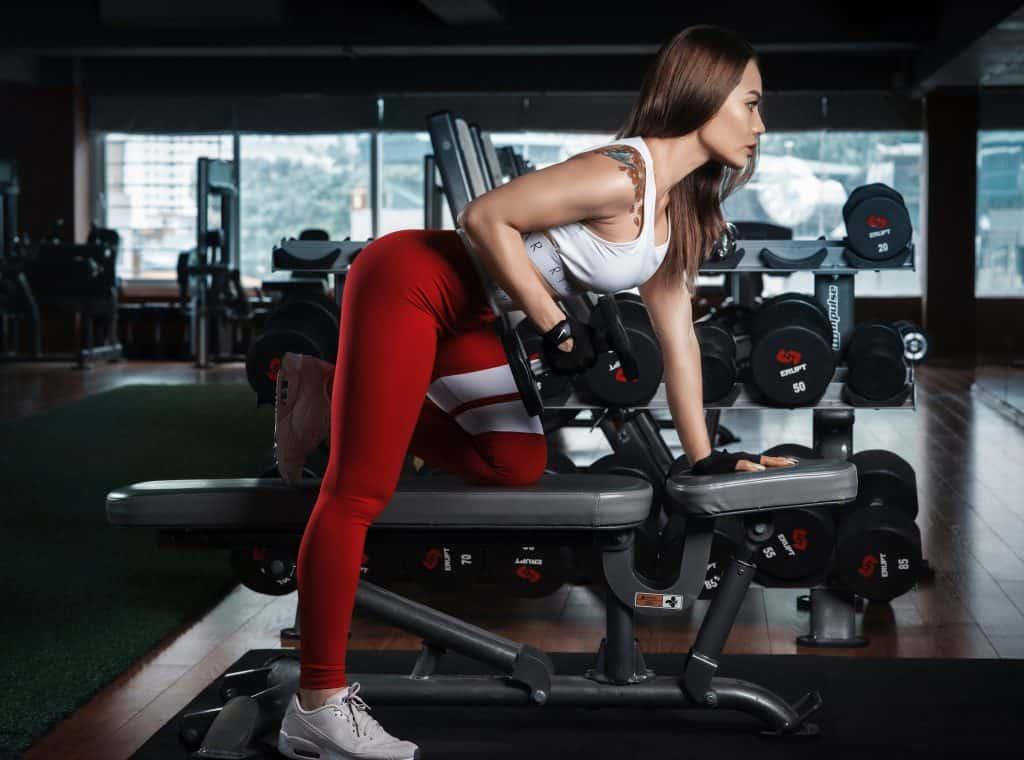 Imagem de uma mulher fazendo musculação.