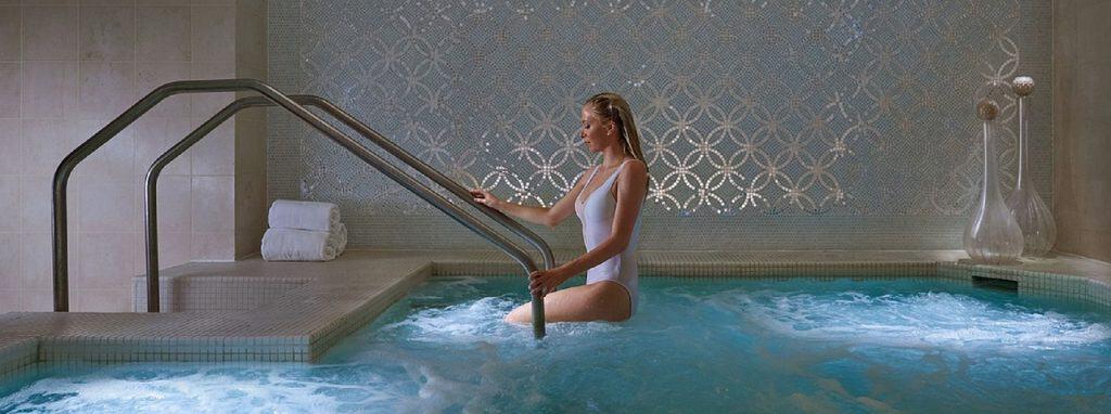 Na foto uma mulher saindo de uma piscina.