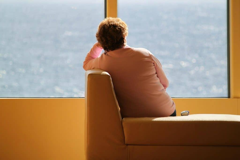 Mulher sentada sozinha de costas.