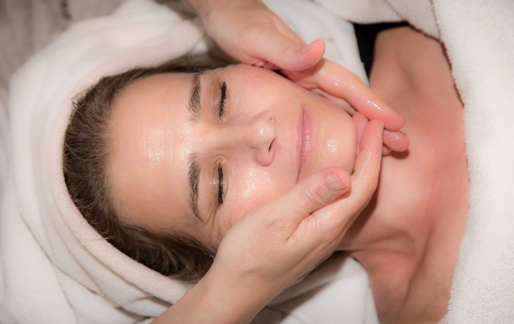 Na foto uma mulher recebendo massagem no rosto.