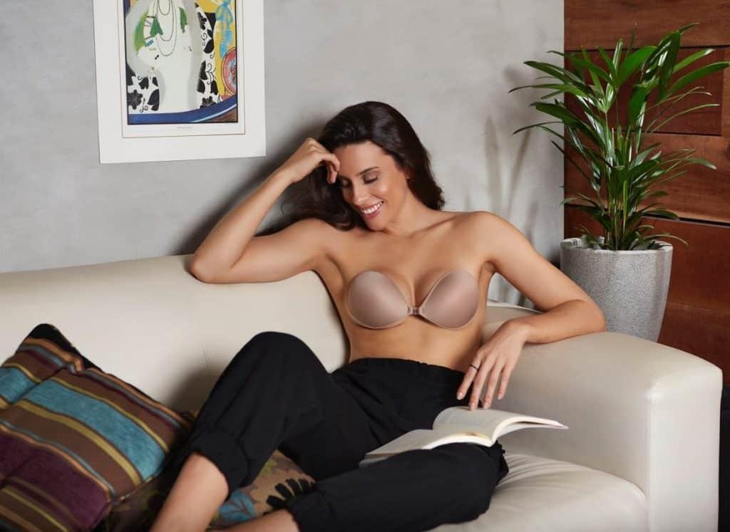 Mulher em sofá com sutiã adesivo.