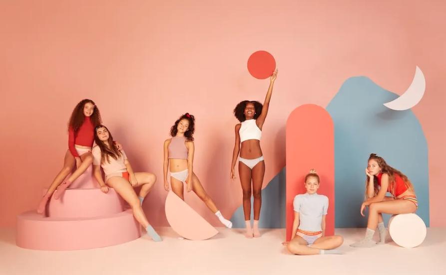 Imagem de mulheres utilizando calcinha absorventes de várias cores.
