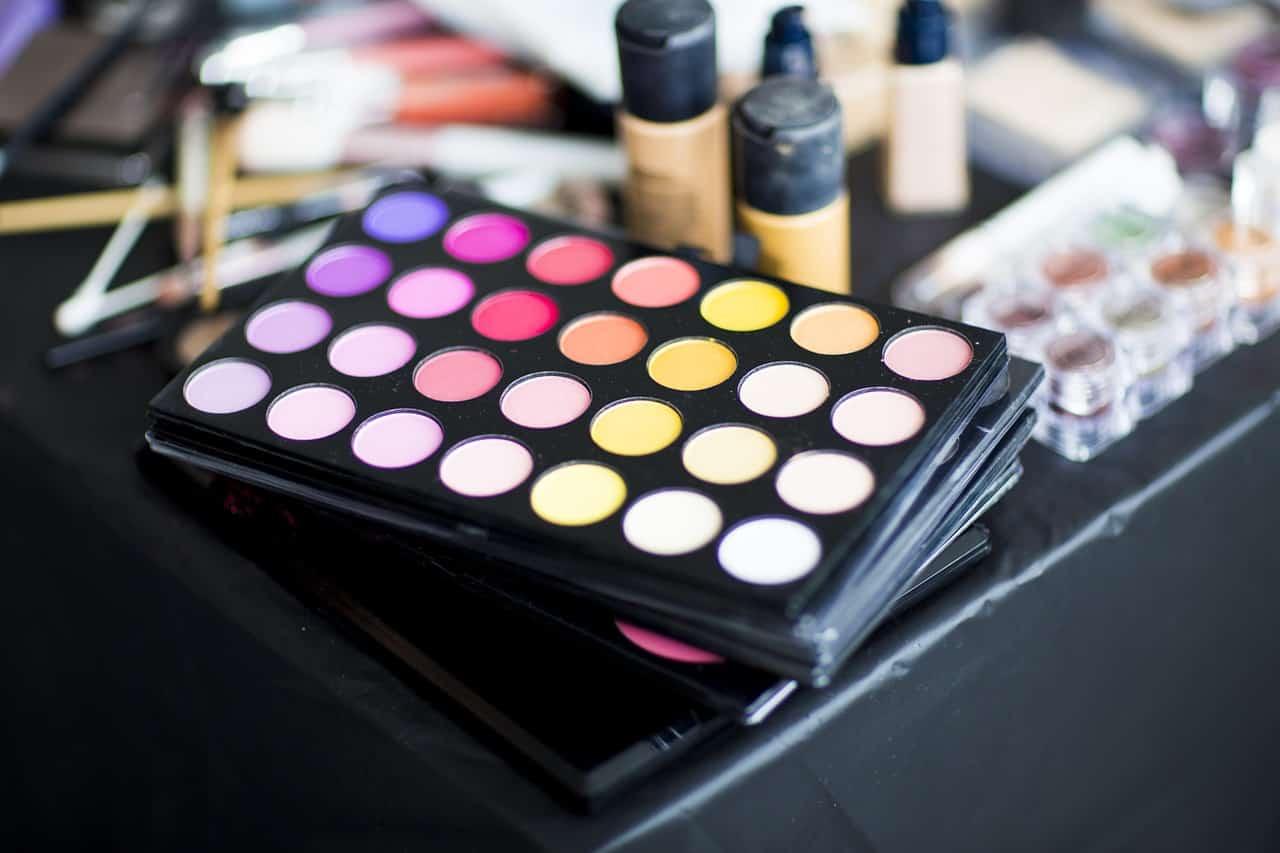 Foto foca em uma paleta de sombras de 28 cores. Ao fundo, é possível notar outros produtos de maquiagem, como bases e pincéis.