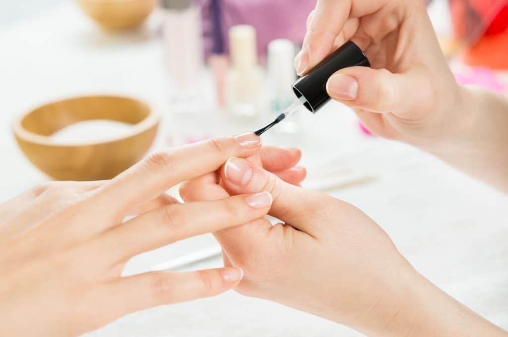 Na foto uma mulher passando esmalte nas unhas de outra.