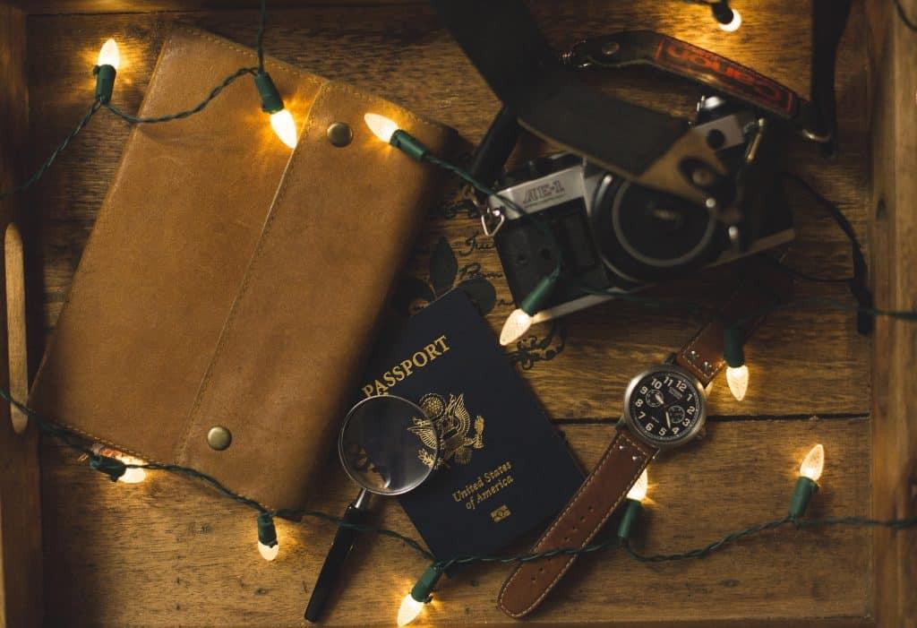Imagem mostra uma mesa de madeira apoiando uma grande carteira de couro ao lado de um passaporte, de uma câmera analógica, um relógio de pulso, uma lupa e algumas luzes de natal.