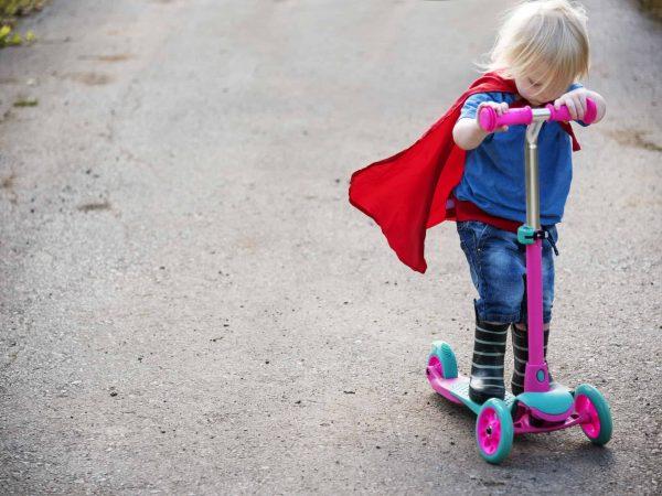 Menino andando com um patinete de 3 rodas.