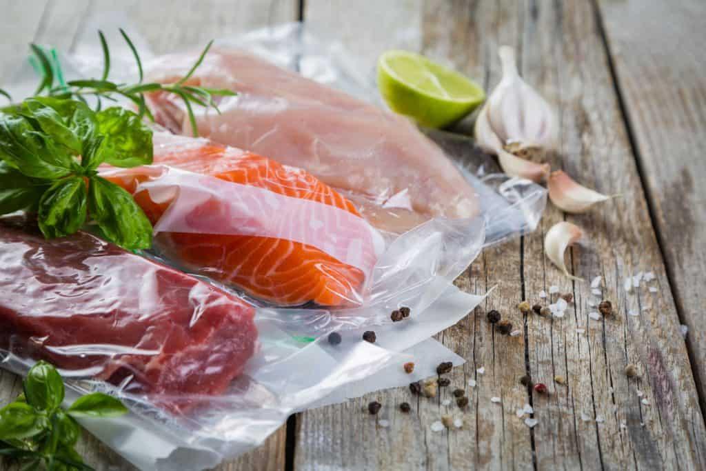 Carnes e peixes embalados a vácuo ao lado de temperos sobre bancada de madeira.