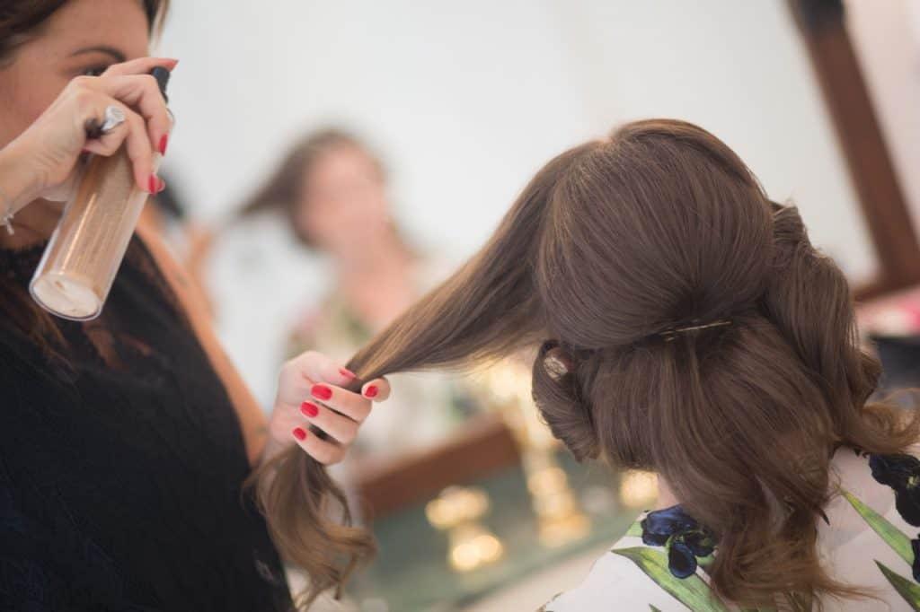 Na foto uma mulher passando fixador no cabelo de outra fazendo penteado.
