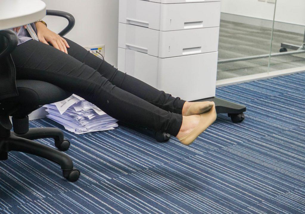 Pernas de uma mulher sentada em uam cadeira do escritório esticando as pernas e descansando os pés.