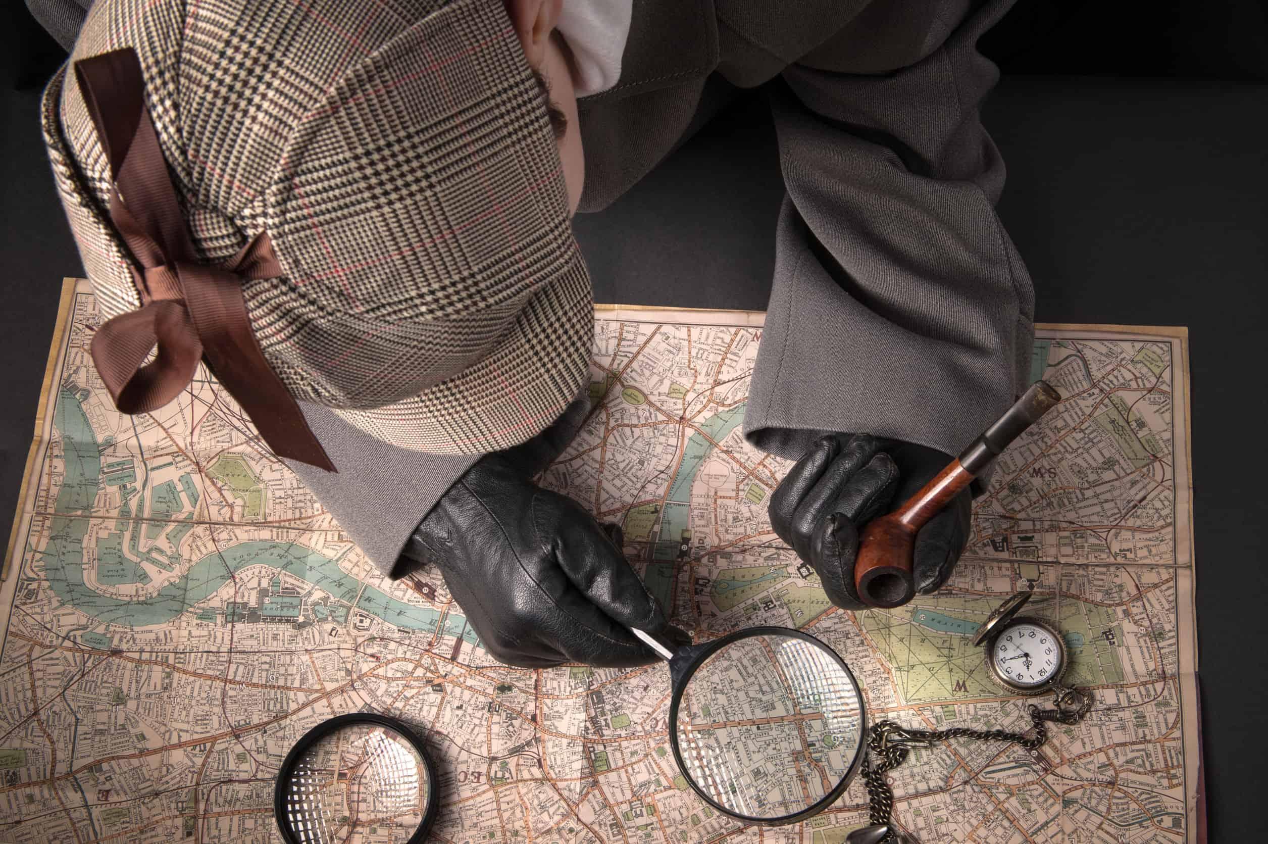 Detetive visto de cima, com boné, luvas e segurando uma caneta em uma mão e uma lupa na outra, analisando um mapa.