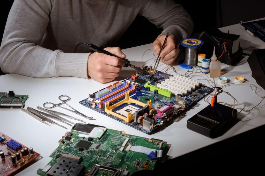 Imagem mostra um homem trabalhando na parte elétrica de uma placa-mãe.