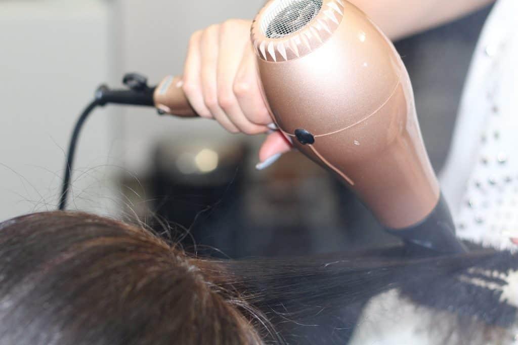 Na foto um cabelo sendo seco com o secador.