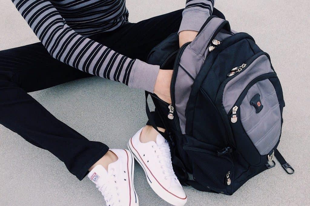 Uma pessoa com as duas mãos dentro de uma mochila personalizada com o zíper aberto.