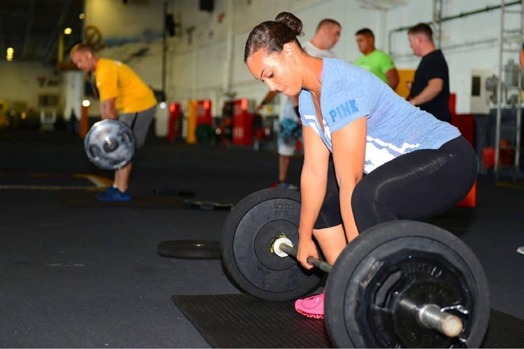 Mulher puxando peso em academia.
