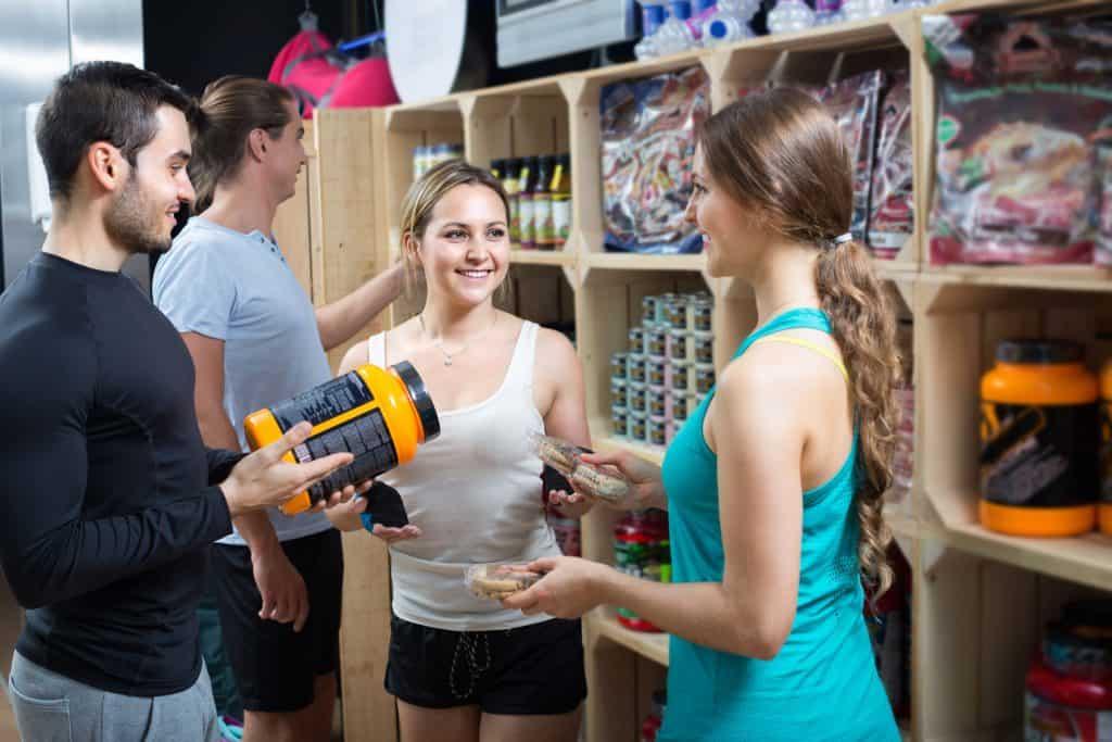 Imagem mostra um casal escolhendo produtos numa loja fitness. O homem está com um pote de suplemento, enquanto a mulher leva uma embalagem de biscoitos em cada mão. Ambos conversam com uma vendedora, que usa luvas de academia.