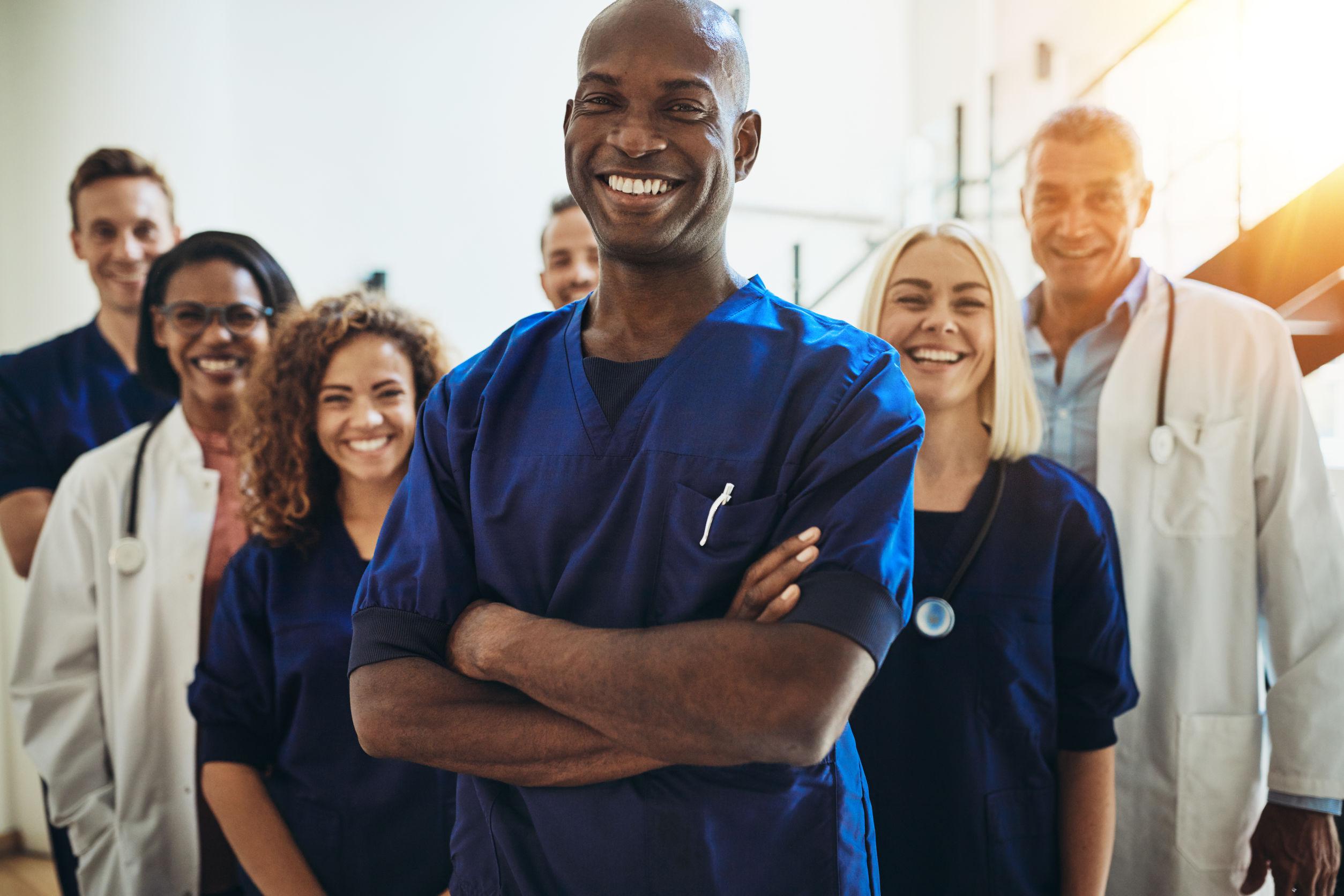Na foto um grupo de médicos usando jaleco e pijama cirúrgico.