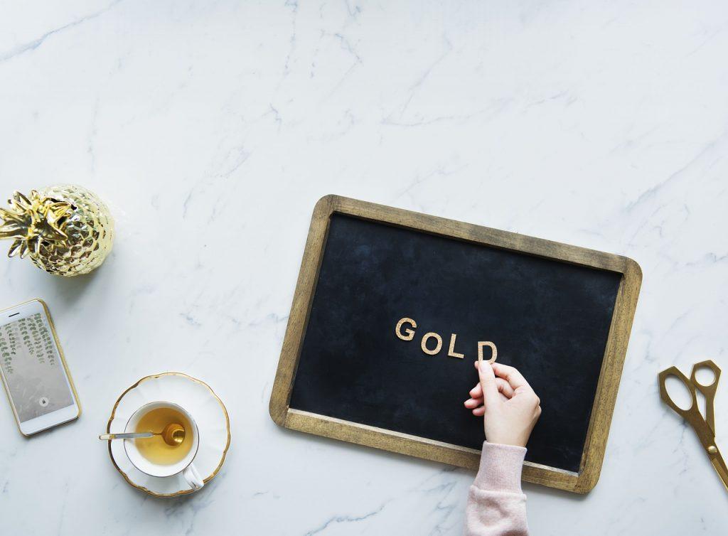 Imagem de pessoa personalizando lima placa decorativa sobre mesa com xícara de chá, celular, tesoura e abacaxi decorativo.