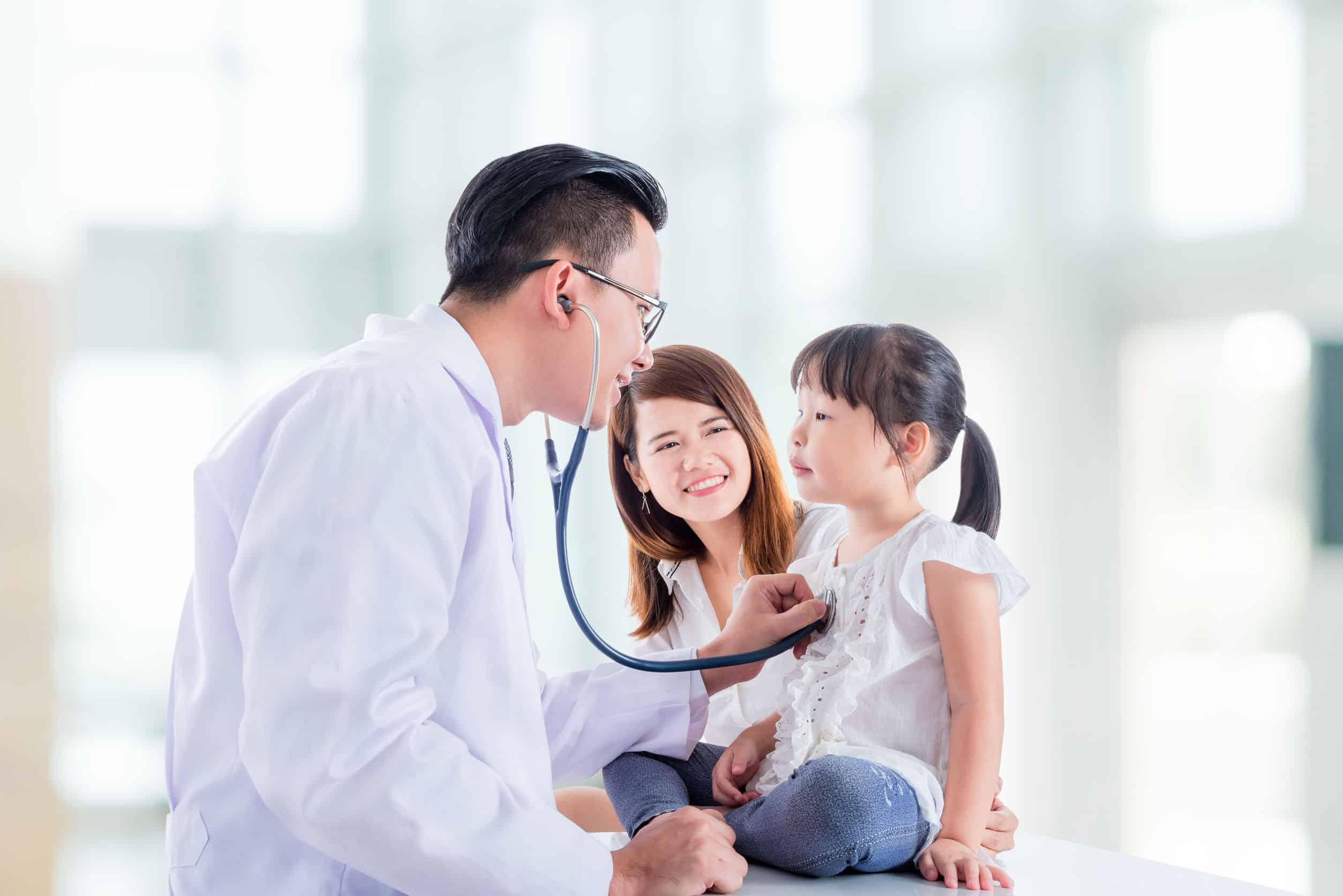 Médico examinando criança com estetoscópio enquanto a mãe sorri ao lado.