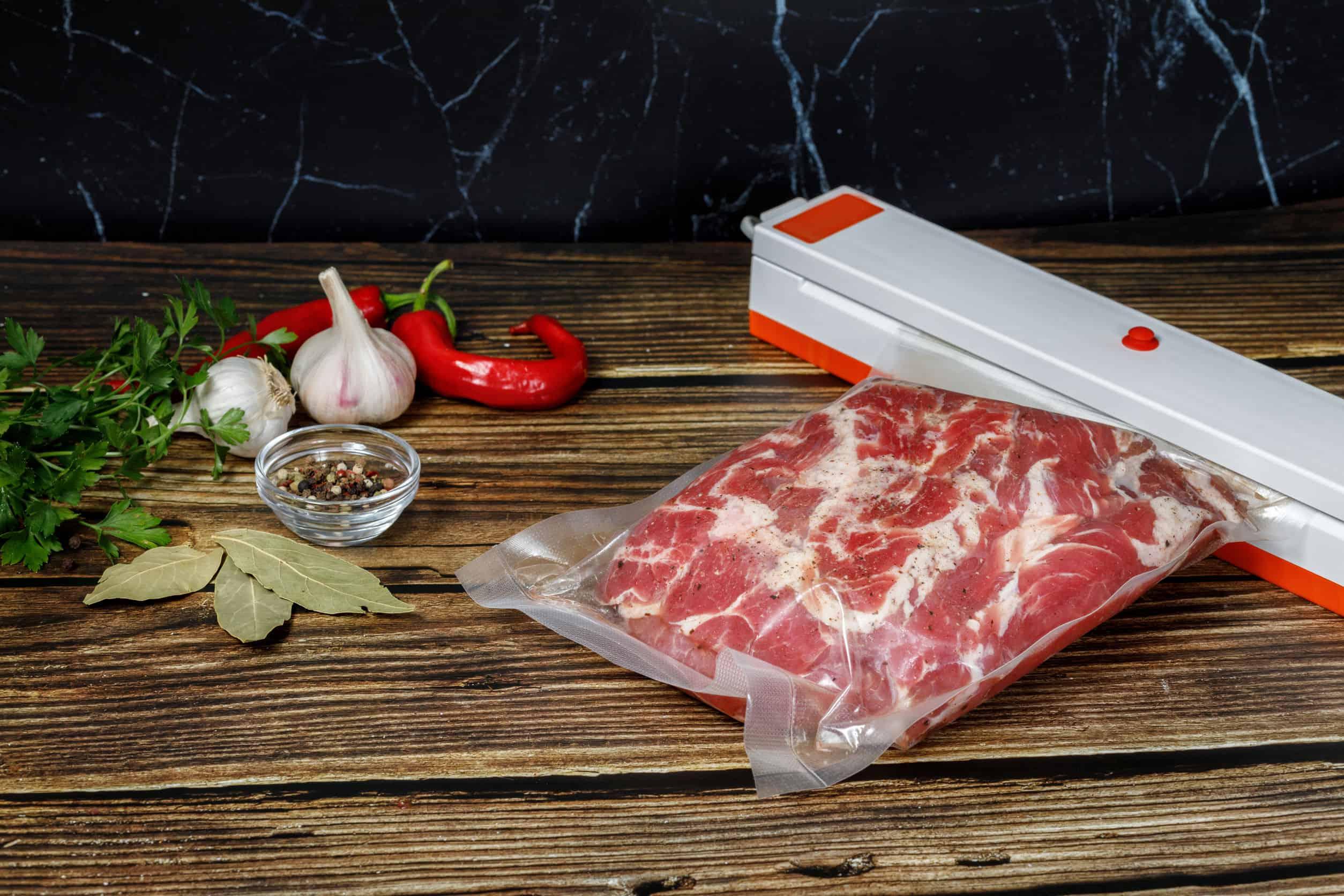 Carne sendo embalada a vácuo sobre bancada de madeira ao lado de temperos.