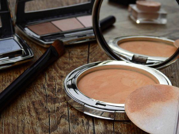 Foto de um pó bronzeador, ao lado de uma esponjinha suja com o produto, um pincel, e duas paletas de sombra.