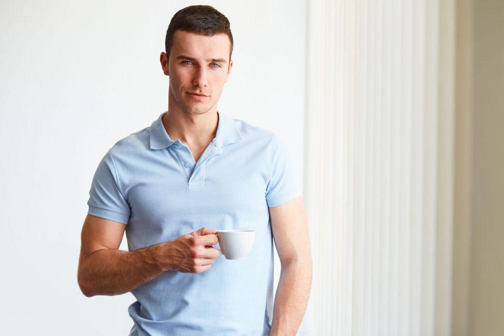 Homem com camiseta polo azul clara e segurando xícara de café.