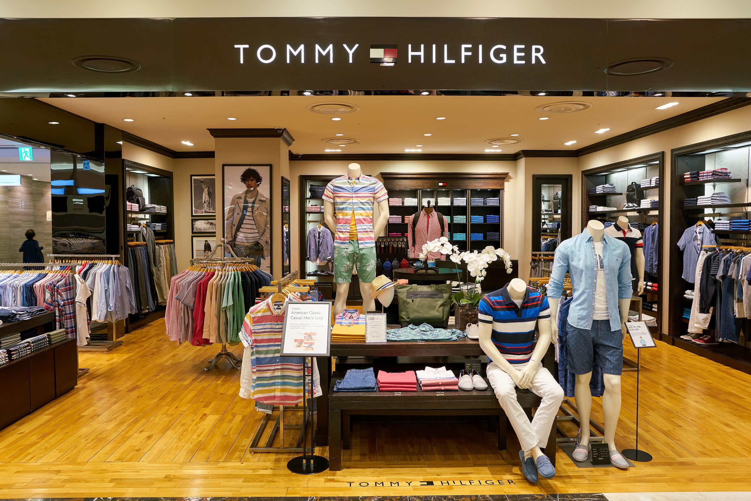 Imagem mostra fachada de uma loja da Tommy com uma camisa polo em destaque.