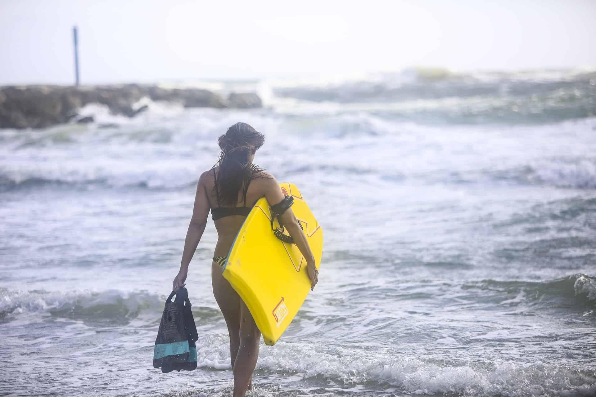Imagem mostra uma mulher caminhando em direção ao mar com uma prancha de bodyboard debaixo de um braço e segurando um par de pés de pato com a mão esquerda.