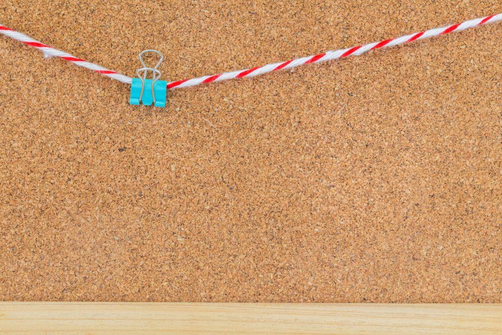 Prendedor de papel preso ao barbante sobre mural de cortiça.