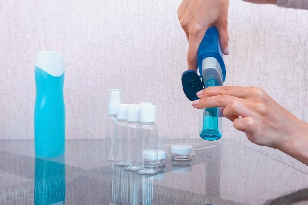 Uma pessoa está preenchendo um frasco com gel de banho. Na mesa de vidro estão outros frascos.