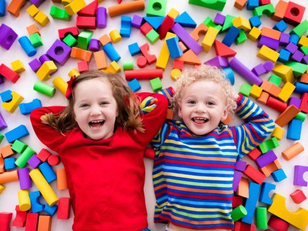 Na foto uma menina e um menino deitados no meio de brinquedos.