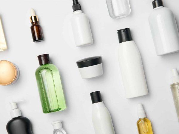 Foto de diversos cosméticos sem rótulo, em tubos e tubos e embalagens diferentes, organizados em uma superfície branca.