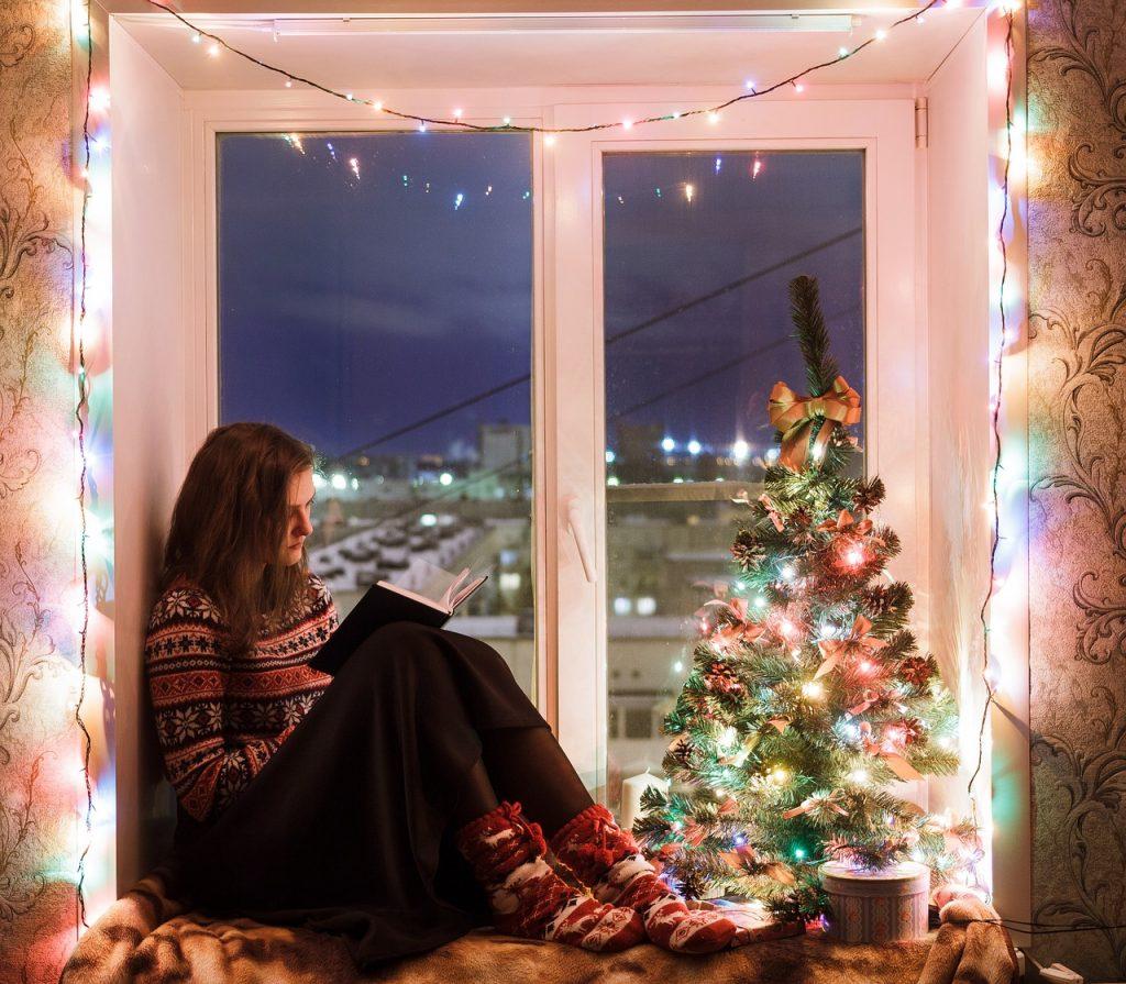 Na foto está uma moça lendo um livro na janela com uma árvore de Natal do lado.
