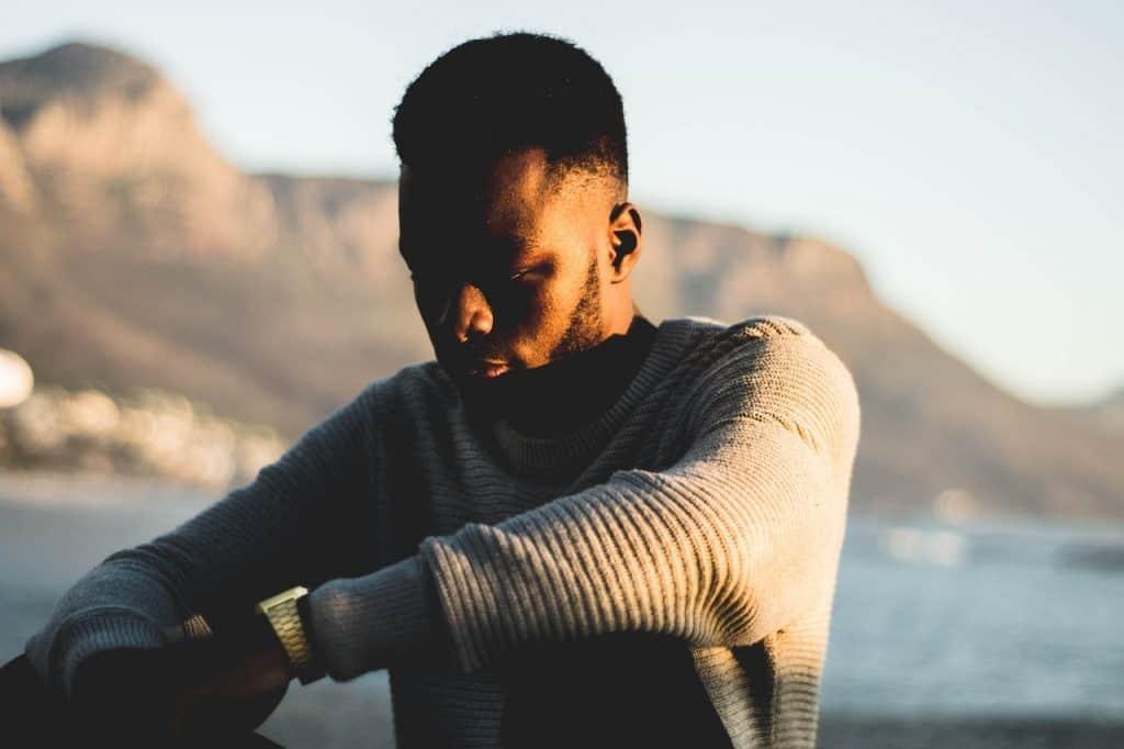 Imagem mostra um homem usando relógio Casio masculino dourado, modelo Vintage. Ele tem os braços apoiados nos joelhos. Ao fundo, uma montanha e o mar, ambos desfocados.