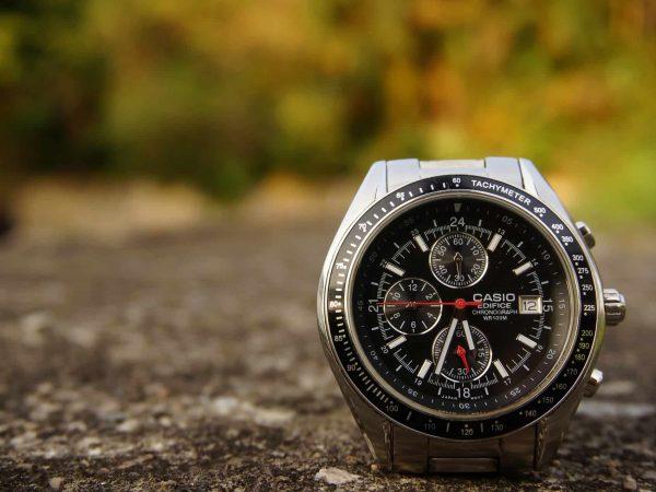 Imagem mostra um relógio casio apoiado verticalmente sobre uma superfície rochosa.