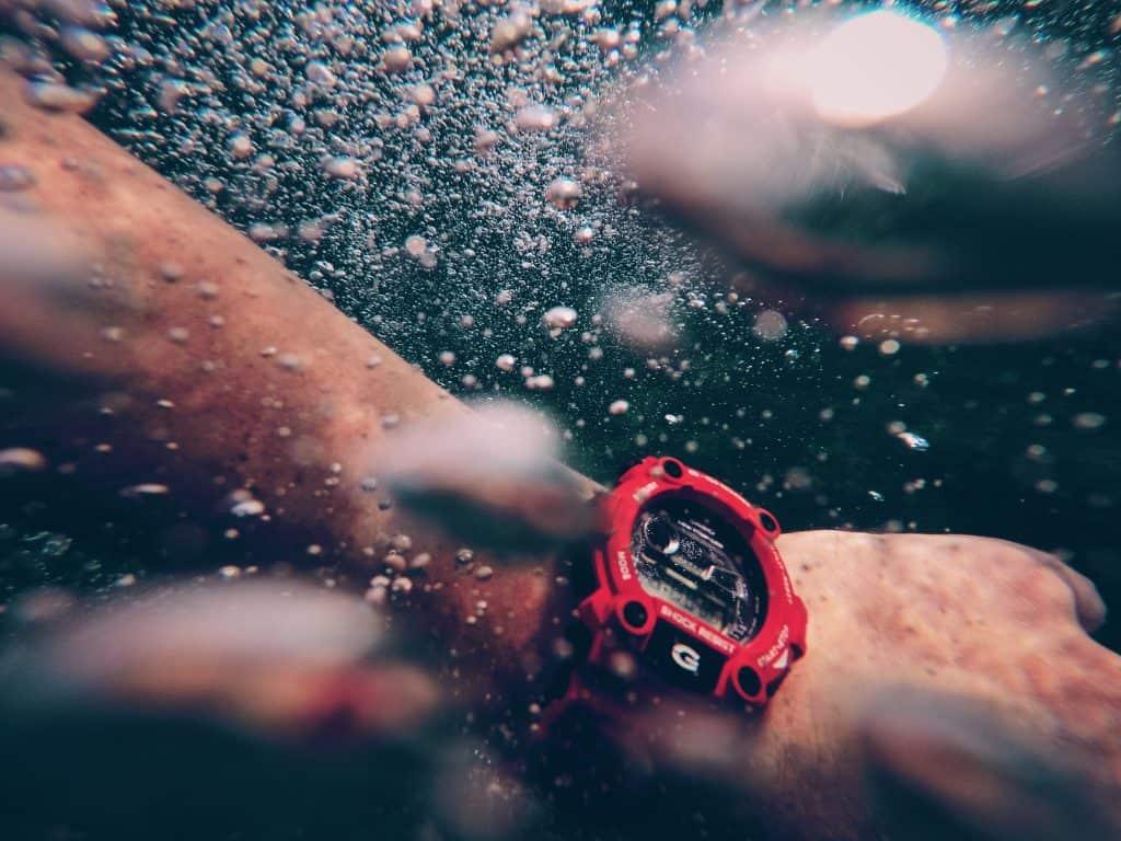 Imagem mostra um relógio Casio masculino modelo G-Shock no pulso esquerdo de um homem submerso no mar.