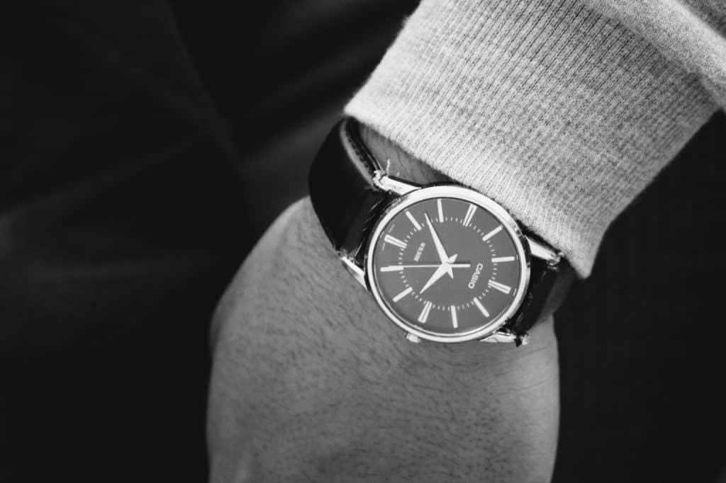 Imagem em preto e branco mostra o close de um relógio no pulso esquerdo do braço de um homem.