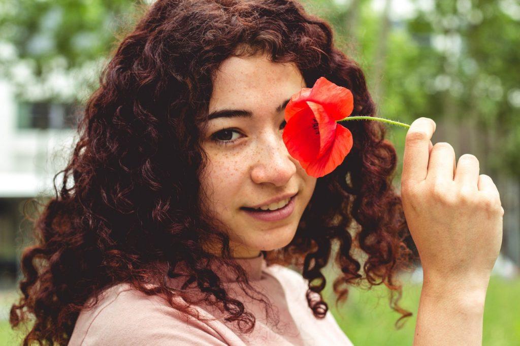 Foto de uma garota ruiva, de cabelos cacheados e sardinha do rosto, segurando um flor vermelha e dando um sorriso discreto.
