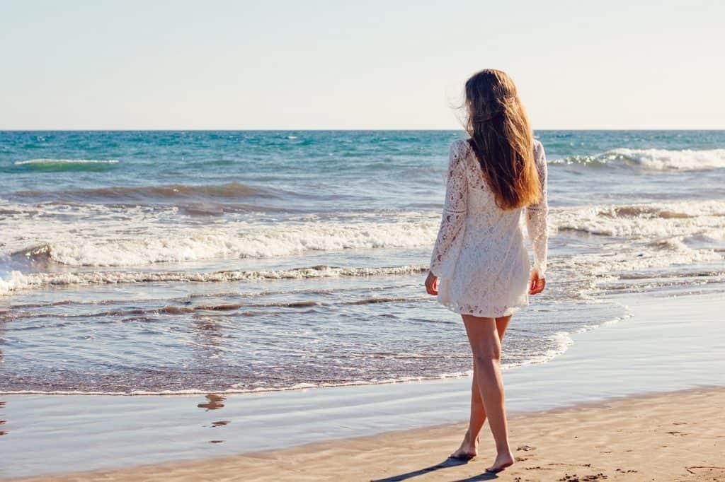 Mulher com saída de praia branca de renda, na beira da praia.