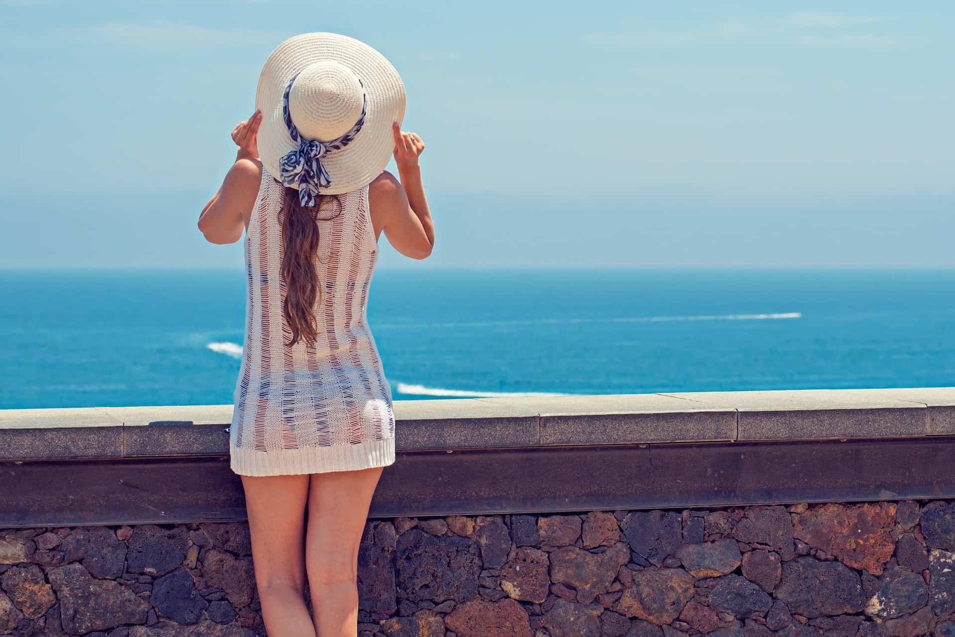 Mulher com saída de praia e chapéu olhando para o mar.