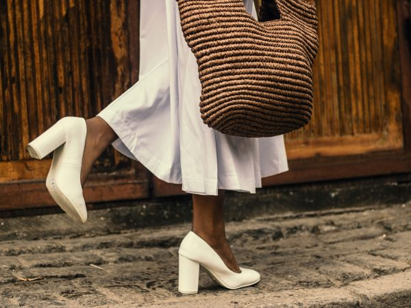 Foto que mostra parte da perna de uma mulher que usa saia midi branca, sapato de salto branco e bolsa de palha. Um de seus pés está no chão, e o outro levemente levantado.