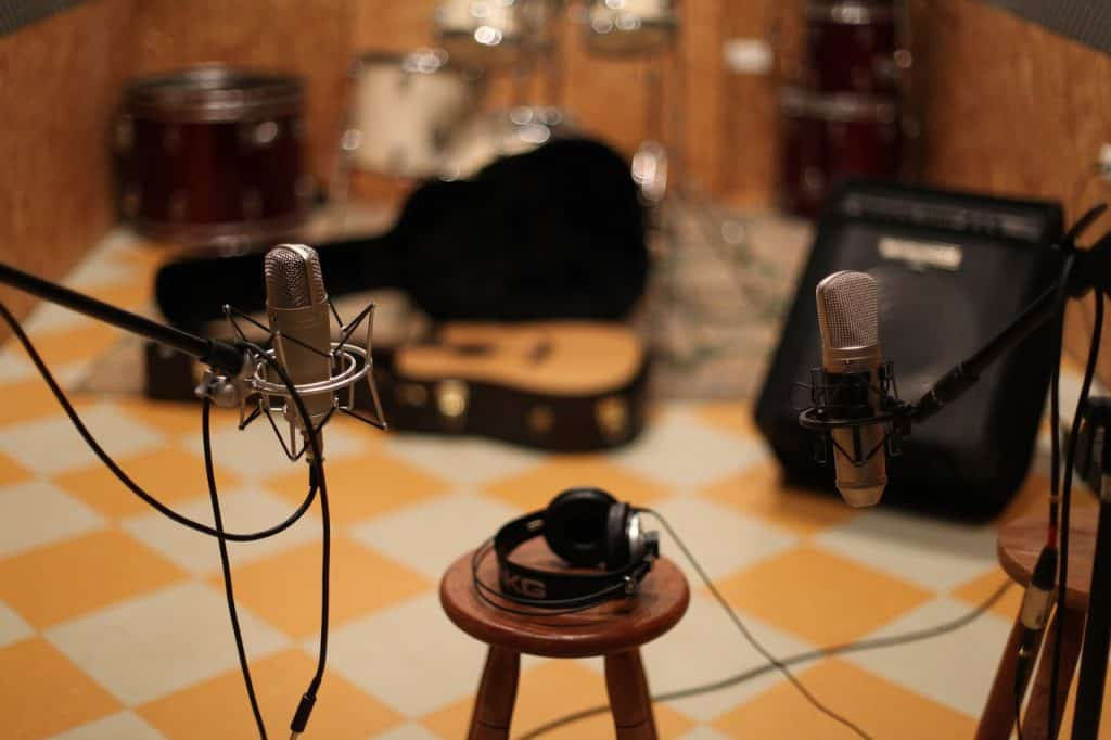 A guitar cover, a guitar, an amplifier, two microphones, two pedestals and a bench form the scene inside a music studio.